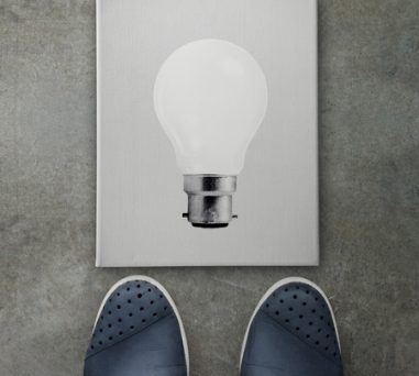 27071240 - hand drawn light bulb on dark canvas board front of business man feet as concept