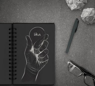 32580999 - hand drawn light bulb with idea word on dark note book as concept